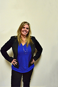 Stacy Burgin property manager at terra point realty, llc standing in a blue shirt with black jacket and black pants
